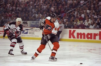 27 Apr 1998:  Defenseman Dave Babych of the Philadelphia Flyers in action against defenseman Jason Woolley of the Buffalo Sabres during their NHL Playoffs game at the Marine Midland Arena in Buffalo, New York.  The Sabres defeated the Flyers 6-1. Mandator