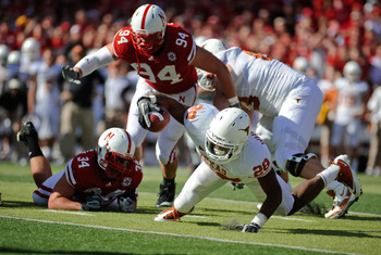 LINCOLN, NE - OCTOBER 16: Texas Longhorn running back Fozzy Whittaker #28 gets tripped up by Nebraska Cornuskers Cameron Meredith #34 and defensive tackle Jared Crick #94 during first half action of their game at Memorial Stadium on October 16, 2010 in Li