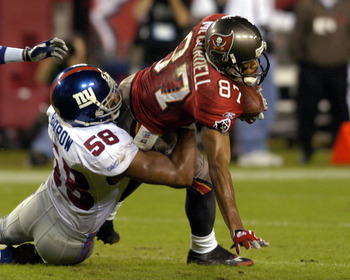 Tampa Bay Buccaneers wide receiver Keenan McCardell grabs a pass and faces a tackle by New York Giants linebacker Michael Barrow  November 24, 2003  at Raymond James Stadium, Tampa.  (Photo by Al Messerschmidt/Getty Images)