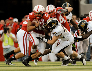 LINCOLN, NE - OCTOBER 30: Running back Roy Helu Jr. #10 of the Nebraska Cornhuskers slipped through the grasp of Andrew Wilson #48 Missouri Tigers Defense during second half action of their game at Memorial Stadium on October 30, 2010 in Lincoln, Nebraska