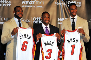 MIAMI - JULY 09:  LeBron James #6, Dwyane Wade #3 and Chris Bosh #1 of the Miami Heat show off their new game jerseys before a press conference after a welcome party at American Airlines Arena on July 9, 2010 in Miami, Florida.  (Photo by Doug Benc/Getty