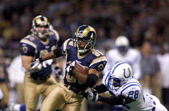 Torry Holt (#88) of the St. Louis Rams is pressured by Idrees Bashir (#28) of the Indianapolis Colts during the game at the Dome at America's Center in St. Louis, Missouri, December 30, 2001. The Colts won 42-17. (Photo by Elsa/Getty Images)