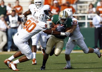 WACO, TX - NOVEMBER 14:  Running back Jarred Salubi #21 of the Baylor Bears carries the ball during in the second half against defensive end Alex Okafor #80 and safety Blake Gideon #21 of the Texas Longhorns on November 14, 2009 at Floyd Casey Stadium in