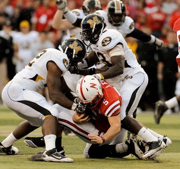 LINCOLN, NE - OCTOBER 30: Quarterback Zac Lee #5 of the Nebraska Cornhuskers takes a hit members of the Missouri Tigers Defense during second half action of their game at Memorial Stadium on October 30, 2010 in Lincoln, Nebraska. Nebraska Defeated Missour