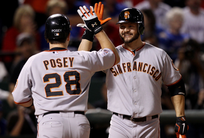 ARLINGTON, TX - OCTOBER 31:  Buster Posey #28 of the San Francisco Giants is congratulated by teammate Cody Ross #13 for his solo home run in eighth inning of Game Four of the 2010 MLB World Series at Rangers Ballpark in Arlington on October 31, 2010 in A