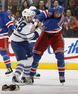 TORONTO - OCTOBER 21: Colton Orr #28 of the Toronto Maple Leafs gets punched by Derek Boogaard #94 of the New York Rangers during game action at the Air Canada Centre October 21, 2010 in Toronto, Ontario, Canada. (Photo by Abelimages/Getty Images)