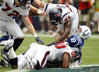 HOUSTON - SEPTEMBER 12:  Quarterback Peyton Manning #18 of the Indianapolis Colts is sacked by defensive ends Antonio Smith #94 and Mario Williams #90 during the NFL season opener at Reliant Stadium on September 12, 2010 in Houston, Texas.  (Photo by Bob