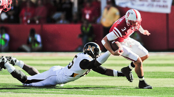 LINCOLN, NE - OCTOBER 30: Quarterback Taylor Martinez #3 of the Nebraska Cornhuskers tries to slip the grip of defensive end Aldon Smith #85 of the Missouri Tigers during first half action of their game at Memorial Stadium on October 30, 2010 in Lincoln,