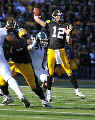 IOWA CITY, IA - OCTOBER 30: Quarterback Ricky Stanzi #12 of the University of Iowa Hawkeyes throw under pressure from defensive end Tyler Hoover #91 of the Michigan State Spartans during the first half of play at Kinnick Stadium on October 30, 2010 in Iow