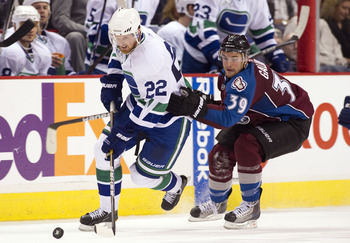 VANCOUVER, CANADA - OCTOBER 26: Daniel Sedin #22 of the Vancouver Canucks tries to break away from TJ Galiardi #39 of the Colorado Avalanche during the third period in NHL action on October 26, 2010 at Rogers Arena in Vancouver, British Columbia, Canada.