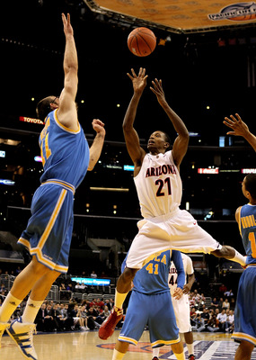 LOS ANGELES, CA - MARCH 11:  Kyle Fogg #21 of the Arizona Wildcats shoots over Reeves Nelson #11 of the UCLA Bruins during the quarterfinals of the Pac-10 Basketball Tournament at Staples Center on March 11, 2010 in Los Angeles, California.  (Photo by Ste