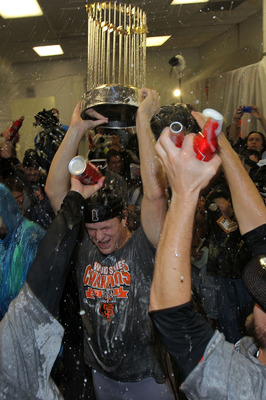 ARLINGTON, TX - NOVEMBER 01:  Matt Cain of the San Francisco Giants holds up the World Series trophy as he celebrates with his teammates in the locker room after the Giants won 3-1 against the Texas Rangers in Game Five of the 2010 MLB World Series at Ran