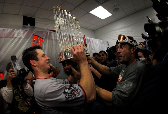 ARLINGTON, TX - NOVEMBER 01:  (L-R) Buster Posey #28 and Andres Torres of the San Francisco Giants celebrates with the trophy in the locker room after the Giants won 3-1 against the Texas Rangers in Game Five of the 2010 MLB World Series at Rangers Ballpa
