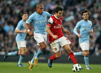 MANCHESTER, ENGLAND - OCTOBER 24:  Cesc Fabregas of Arsenal holds off Nigel De Jong of City during the Barclays Premier League match between Manchester City and Arsenal at City of Manchester Stadium on October 24, 2010 in Manchester, England.  (Photo by R