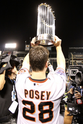 ARLINGTON, TX - NOVEMBER 01:  Buster Posey #28 of the San Francisco Giants celebrates with the World Series Championship trophy after the Giants won 3-1 the Texas Rangers in Game Five of the 2010 MLB World Series at Rangers Ballpark in Arlington on Novemb