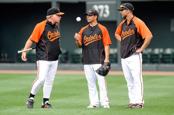 BALTIMORE - AUGUST 03:  Manager Buck Showalter of the Baltimore Orioles talks with Brian Roberts #1 and Nick Markakis #21 before the game against the Los Angeles Angels of Anaheim at Camden Yards on August 3, 2010 in Baltimore, Maryland.  (Photo by Greg F