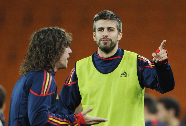 JOHANNESBURG, SOUTH AFRICA - JULY 10:  Gerard Pique of Spain chats with Carlos Puyol (L) during a Spain training session, ahead of the 2010 FIFA World Cup Final, at Soccer City Stadium on July 10, 2010 in Johannesburg, South Africa.  (Photo by Jasper Juin