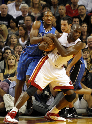MIAMI - OCTOBER 29:  Guard Chris Duhon #25 of the Orlando Magic has a jump ball with center Joel Anthony #50 of the Miami Heat at American Airlines Arena on October 29, 2010 in Miami, Florida.  NOTE TO USER: User expressly acknowledges and agrees that, by