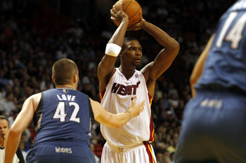 MIAMI - NOVEMBER 02:  Forward Chris Bosh #1 of the Miami Heat passes against center Kevin Love #42 of the Minnesota Wolves at American Airlines Arena on November 2, 2010 in Miami, Florida. NOTE TO USER: User expressly acknowledges and agrees that, by down