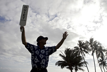 UNITED STATES - JANUARY 11:  A volunteer holds up a 'QUIET' sign on the 17th tee during the first round of the Sony Open held at the Waialae Country Club in Honolulu, Hawaii on January 11, 2007.  (Photo by Marco Garcia/Getty Images)