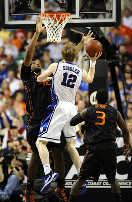 GREENSBORO, NC - MARCH 13:  Kyle Singler #12 of the Duke Blue Devils puts up a shot between Reggie Johnson #32 and Malcolm Grant #3  of the University of Miami Hurricanes in their semifinal game in the 2010 ACC Men's Basketball Tournament at the Greensbor