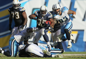 SAN DIEGO - OCTOBER 31:  Running back Mike Tolbert #35 of the San Diego Chargers carries the ball while being pursued by Jason Babin #93 of the Tennessee Titans in the fourth quarter at Qualcomm Stadium on October 31, 2010 in San Diego, California. The Ch