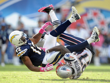 SAN DIEGO - OCTOBER 24:  Patrick Crayton #12 of the San Diego Chargers takes a hit from Kyle Arrington #27 of the New England Patriots at Qualcomm Stadium on October 24, 2010 in San Diego, California.  (Photo by Harry How/Getty Images)