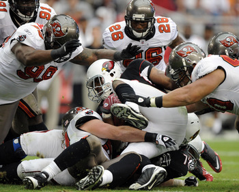 GLENDALE, AZ - OCTOBER 31:  Beanie Wells #26 of the Arizona Cardinals is tackled by Roy Miller #90, Ryan Sims #98 and Sean Jones #26 of the Tampa Bay Buccaneers at University of Phoenix Stadium on October 31, 2010 in Glendale, Arizona.  (Photo by Harry Ho