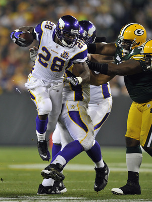 GREEN BAY, WI - OCTOBER 24:  Adrian Peterson #28 of the Minnesota Vikings leaps in the air for extra yardage against the Green Bay Packers at Lambeau Field on October 24, 2010 in Green Bay, Wisconsin. (Photo by Jim Prisching/Getty Images)