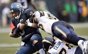 SEATTLE - DECEMBER 24:  Quarterback Matt Hasselbeck #8 of the Seattle Seahawks is sacked by linebacker Shawne Merriman #56 and defensive end Jacques Cesaire #74 of the San Diego Chargers on December 24, 2006 at Qwest Field in Seattle, Washington.  (Photo