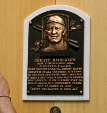 COOPERSTOWN, NY - JULY 29:  A baseball fan photograghs the plaque of Christy Mathewson at the National Baseball Hall of Fame and Museum during the Baseball Hall of Fame weekend on July 29, 2006 in Cooperstown, New York.  (Photo by Jim McIsaac/Getty Images