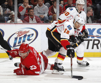 DETROIT - OCTOBER 21: Jarome Iginla #12 of the Calgary Flames controls the puck next to Brad Stuart #23 of the Detroit Red Wings on October 21, 2010 at Joe Louis Arena in Detroit, Michigan. Detroit won the game 4-2.  (Photo by Gregory Shamus/Getty Images)
