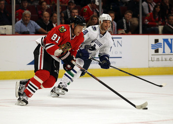 CHICAGO - OCTOBER 20: Marian Hossa #81 of the Chicago Blackhawks controls the puck under pressure from Peter Schaefer #18 of the Vancouver Canucks at the United Center on October 20, 2010 in Chicago, Illinois. The Blackhawks defeated the Canucks 2-1 in a