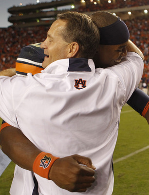 AUBURN - OCTOBER 16:  Head coach Gene Chizik of the Auburn Tigers hugs quarterback Cam Newton #2 after the game against the Arkansas Razorbacks at Jordan-Hare Stadium on October 16, 2010 in Auburn, Alabama.  The Tigers beat the Razorbacks 65-43.  (Photo b