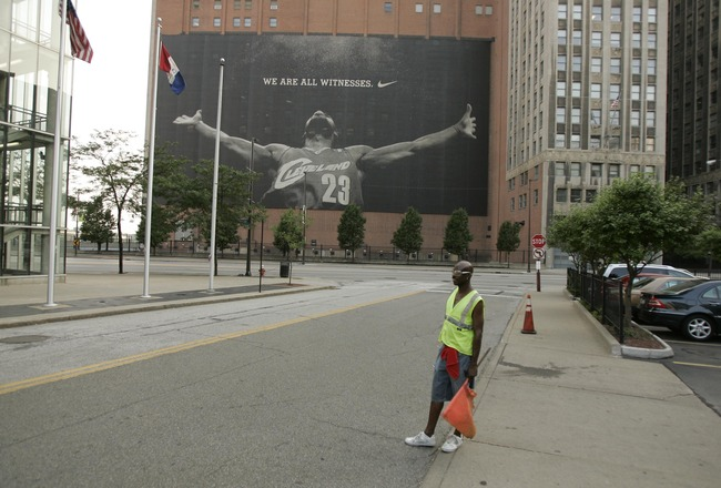 CLEVELAND - JULY 8:  A parking attendant stands near a larger than life photograph of LeBron James July 8, 2010 in Cleveland, Ohio. The two-time Most Valuable Player has the choice of remaining with the Cleveland Cavaliers or signing with a new team. (Pho