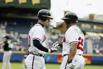 ATLANTA - APRIL 7:  Andruw Jones #25 of the Atlanta Braves congratulates teammate Chipper Jones #10 on hitting a solo home run during the game against the Florida Marlins at Turner Field on April 7, 2003 in Atlanta, Georgia.  The Braves won 3-0.  (Photo b