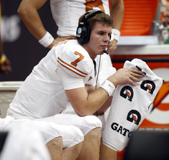HOUSTON - SEPTEMBER 04:  Quarterback Garrett Gilbert #7 of the Texas Longhorns talks with coaches in the press box during a game against the Rice Owls at Reliant Stadium on September 4, 2010 in Houston, Texas. Texas beat Rice 34-17.  (Photo by Bob Levey/G