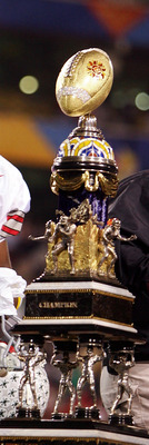 TEMPE, AZ - JANUARY 02:  Quarterback Troy Smith #10 of the Ohio State Buckeyes holds up a fist as he stands next to the trophy after the Buckeyes defeated the Notre Dame Fighting Irish in the Tostito's Fiesta Bowl at Sun Devil Stadium on January 2, 2006 i