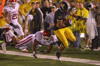 COLUMBIA, MISSOURI - OCTOBER 23: Kendial Lawrence #4 of the Missouri Tigers gets past Jonathan Nelson #3 of the Oklahoma Sooners at Faurot Field/Memorial Stadium on October 23, 2010 in Columbia, Missouri.  The Tigers beat the Sooners 36-27.  (Photo by Dil