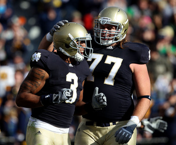SOUTH BEND, IN - OCTOBER 30: Michael Floyd #3 and Matt Romine #77 of the Notre Dame Fighting Irish celebrate Floyd's touchdown catch against the Tulsa Golden Hurricane at Notre Dame Stadium on October 30, 2010 in South Bend, Indiana. (Photo by Jonathan Da