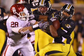 COLUMBIA, MISSOURI - OCTOBER 23: De'Vion Moore #26 of the Missouri Tigers looks to get past Travis Lewis #28 of the Oklahoma Sooners at Faurot Field/Memorial Stadium on October 23, 2010 in Columbia, Missouri.  The Tigers beat the Sooners 36-27.  (Photo by