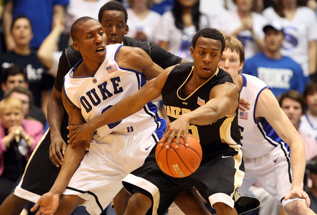 DURHAM, NC - JANUARY 17:  Ishmael Smith #10 and teammate Al-Farouq Aminu #1 of the Wake Forest Demon Deacons keep the ball away from Nolan Smith #2 and Kyle Singler #12 of the Duke Blue Devils during their game on January 17, 2010 in Durham, North Carolin