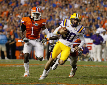 GAINESVILLE, FL - OCTOBER 09:  Punter Josh Jasper #30 of the Louisiana State University Tigers runs a fake punt for yardage past Ahmad Black #35 and Janoris Jenkins #1 of the Florida Gators during the game at Ben Hill Griffin Stadium on October 9, 2010 in