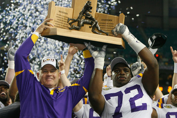 ATLANTA - DECEMBER 01:  Head coach Les Miles and Glenn Dorsey #72  of the Louisiana State University Tigers celebrate with the SEC trophy after defeating the University of Tennessee Volunteers 21-14 in the SEC Championship game on December 1, 2007 at the