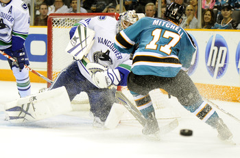 SAN JOSE, CA - SEPTEMBER 29: Goalie Eddie Lack #76 of the Vancouver Canucks clears the puck through the legs of Torrey Mitchell #17 of the San Jose Sharks during their preseason game against the San Jose Sharks at the HP Pavilion on September 29, 2010 in