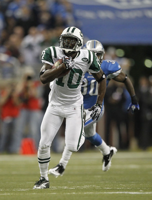 DETROIT - NOVEMBER 07:  Santonio Holmes #10 of the New York Jets catches a 54 yard pass in overtime and is tackled by Landon Johnson #54 of the Detroit Lions during the overtime period at Ford Field on November 7, 2010 in Detroit, Michigan. The Jets defea