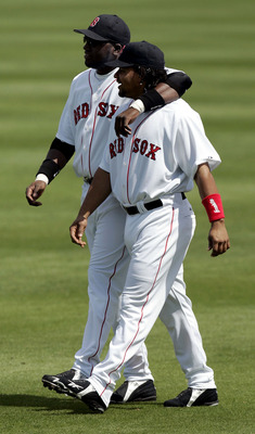 FORT MYERS, FL - MARCH 6:  David Ortiz #34 and teammate Manny Ramirez #34 of the Boston Red Sox walk in the outfield before the start of their game against the Philadelphia Phillies on March 6, 2005 at Wilbur Billy Smith Field in Fort Myers, Florida.  (Ph