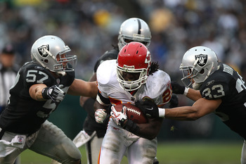OAKLAND, CA - NOVEMBER 07:  Jamaal Charles #25 of the Kansas City Chiefs runs against Tyvon Branch #33 and Ricky Brown #57 of the Oakland Raiders during an NFL game at Oakland-Alameda County Coliseum on November 7, 2010 in Oakland, California.  (Photo by