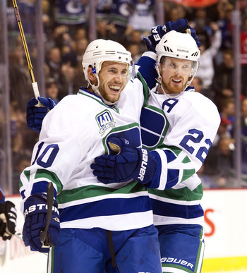 VANCOUVER, CANADA - OCTOBER 26: Jeff Tambellini #10 of the Vancouver Canucks is congratulated by Daniel Sedin #22 after scoring against the Colorado Avalanche during the first period in NHL action on October 26, 2010 at Rogers Arena in Vancouver, British