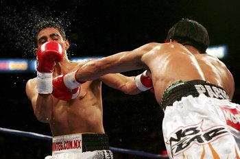 LAS VEGAS - NOVEMBER 18:  (R-L) Manny Pacquiao of the Philippines connects with a left to the face of Erik Morales of Mexico during their super featherweight bout at the Thomas & Mack Center on November 18, 2006 in Las Vegas, Nevada. Pacquiao won after a